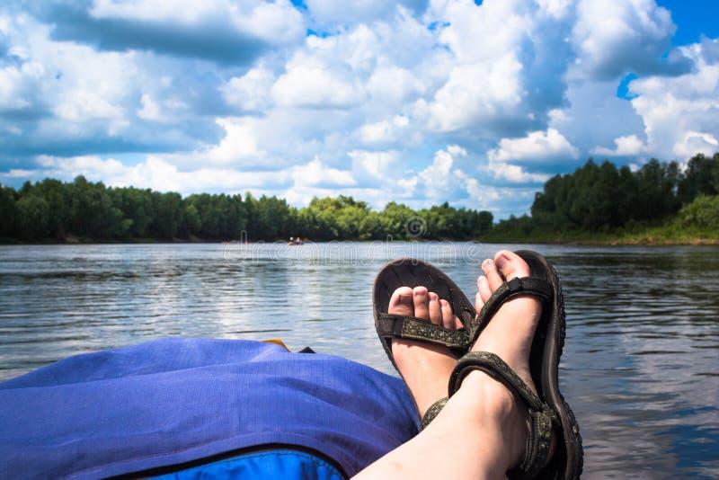 Las piernas están mintiendo en el kajak Río Kayaking en naturaleza hermosa del verano imagen de archivo