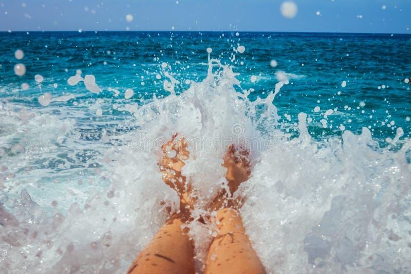 Las piernas femeninas cubiertas con un chapoteo de un mar agitan fotografía de archivo