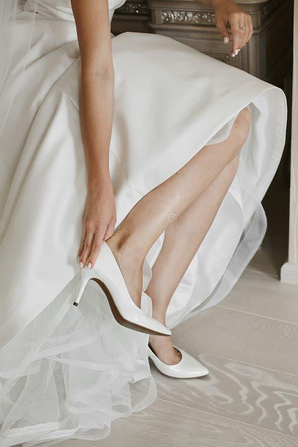 Las piernas femeninas hermosas en zapatos elegantes en un tacón alto, la novia ponen encendido casarse los zapatos en el tacón al imagen de archivo libre de regalías