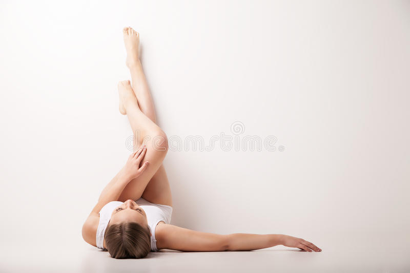Las piernas hermosas de la mujer aumentaron para arriba arriba la mentira imagenes de archivo