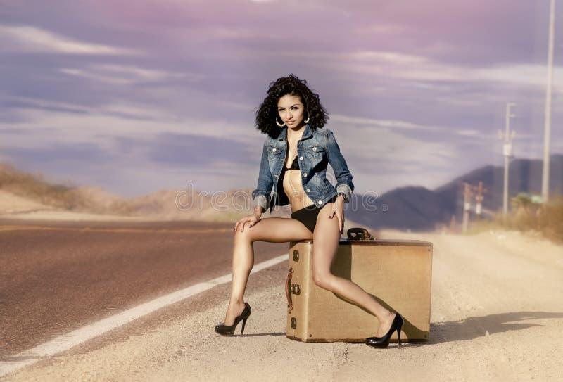 Las piernas largas de la mujer que se sientan en la maleta del equipaje abandonan fotografía de archivo