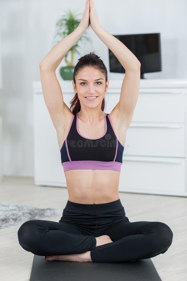 Las piernas practicantes de la yoga de la muchacha cruzaron los brazos aumentados en la posición del rezo fotografía de archivo libre de regalías