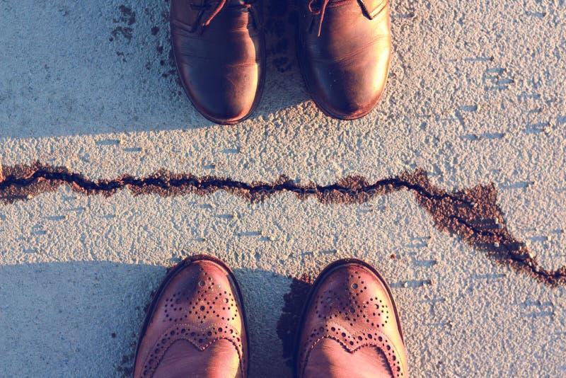 Las piernas se calzan en los zapatos de cuero del color marrón y negro, que son separados por una grieta en el asfalto foto de archivo libre de regalías