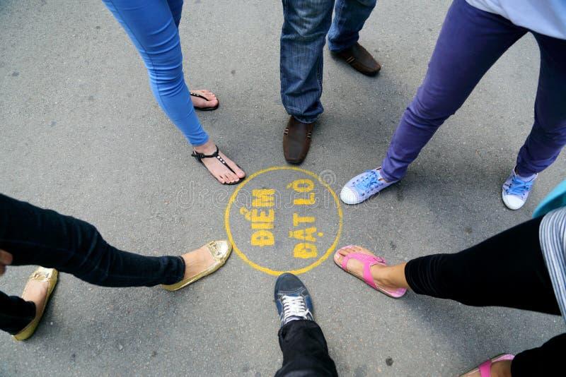Las piernas y los zapatos vienen juntos cerca de un círculo con palabra vietnamita imágenes de archivo libres de regalías
