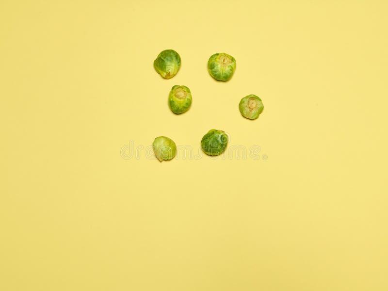 Las pilas de coles de Bruselas en un fondo amarillo fotografía de archivo