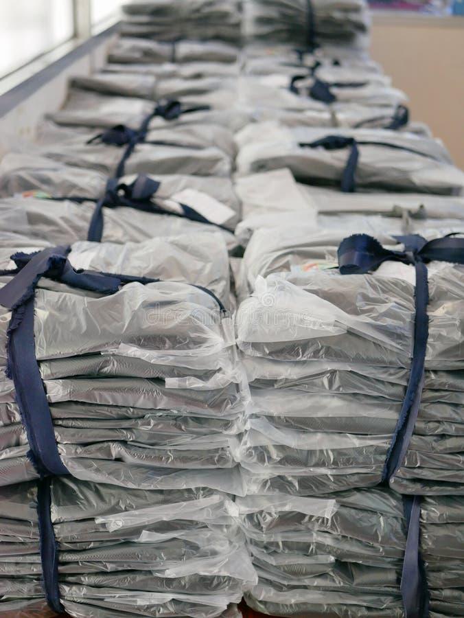 Las pilas de ropa embalaron en las bolsas de plástico listas para ser enviado/para ser distribuido fotos de archivo libres de regalías