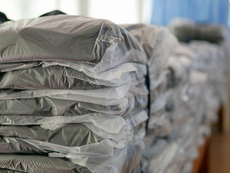 Las pilas de ropa embalaron en las bolsas de plástico listas para ser enviado/para ser distribuido fotografía de archivo