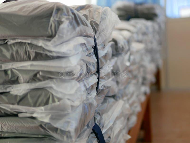Las pilas de ropa embalaron en las bolsas de plástico listas para ser enviado/para ser distribuido foto de archivo libre de regalías