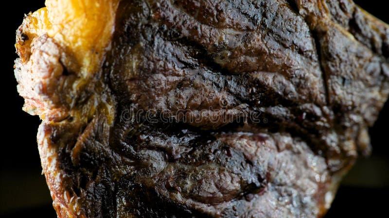 Las pimientas alistan el filete del T-hueso en una placa imagenes de archivo