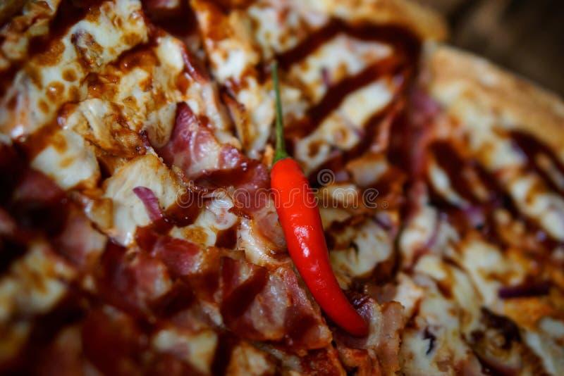 Las pimientas de chile rojo están mintiendo en una salsa casera de la barbacoa-pizza Luz del d?a Primer foto de archivo