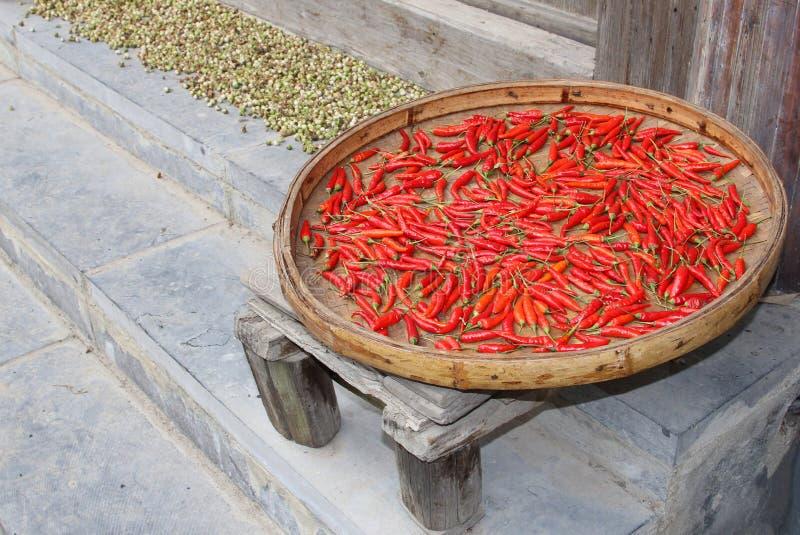 Las pimientas rojas se están secando en el sol en un pueblo chino viejo foto de archivo libre de regalías