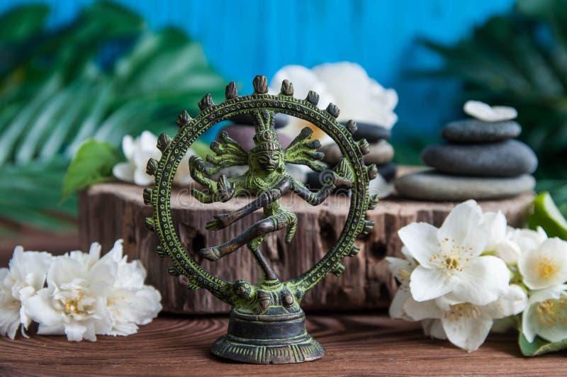 Las pirámides de ZENES Stone grises con las flores, verde se van en fondo de madera Concepto de armonía, de balanza y de meditaci fotos de archivo