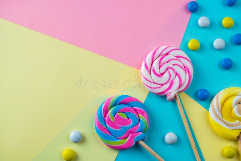 Las piruletas brillantes y el fondo dulces coloridos de los caramelos plano ponen imagen de archivo
