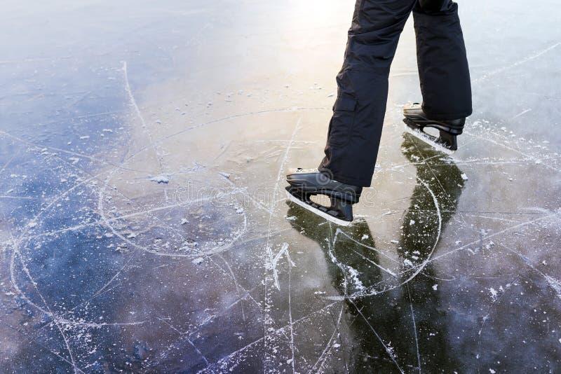 Las pistas del patinaje de hielo, un hombre se colocan al lado de ella foto de archivo libre de regalías