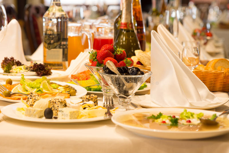 Las placas de comen y los aperitivos en una tabla de comida fría imagen de archivo