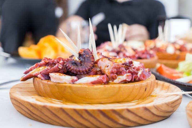 Las placas de madera deliciosas del estilo gallego cocinaron el pulpo con paprika y aceite de oliva Pulpo un la Gallega fotos de archivo