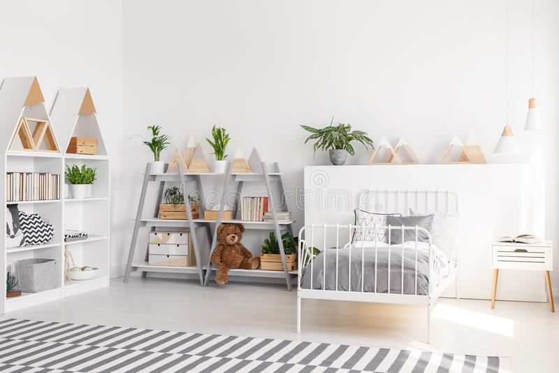Las plantas y la felpa juegan en estantes en interi del dormitorio del ` s del niño del scandi imágenes de archivo libres de regalías