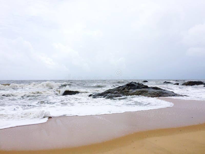 Las playas arenosas de Kundapura con las rocas y las ondas espumosas fotos de archivo libres de regalías
