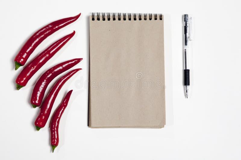 Las postales para las recetas Bloc de bocetos, pluma y pimienta candente como marco en un fondo blanco fotos de archivo