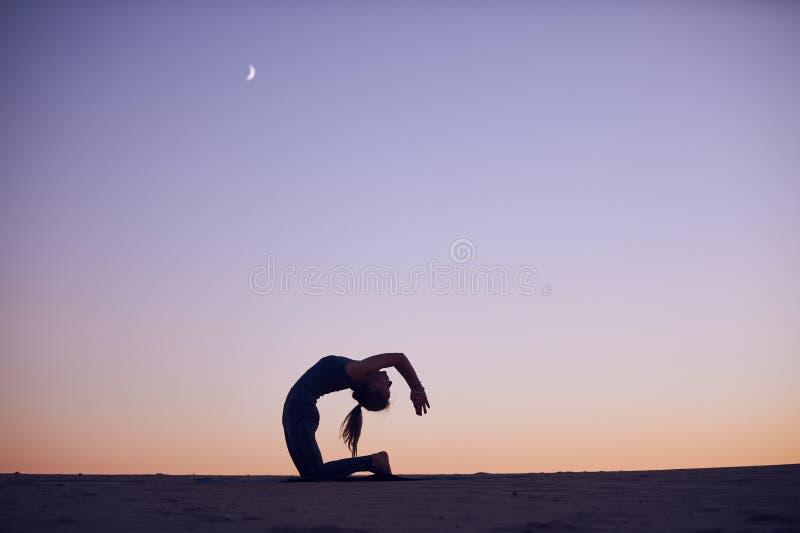 Las prácticas hermosas de la mujer joven avanzaron la variación de la actitud del camello - Ustrasana en el desierto en la noche foto de archivo