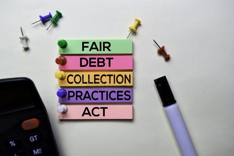 Las prácticas justas del reembolso de la deuda actúan - texto de FDCPA en las notas pegajosas aisladas en el escritorio de oficin fotografía de archivo libre de regalías
