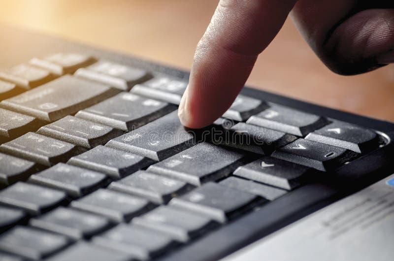 Las prensas a del hombre de negocios entran en el botón en el teclado negro con luz del sol foto de archivo