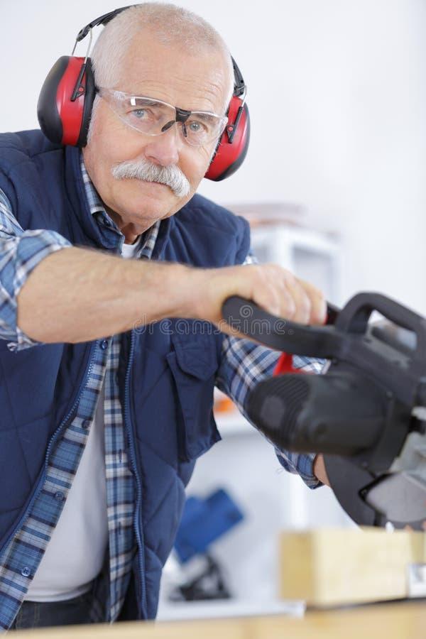 Las protecciones auditivas del hombre que llevaban mayor mientras que usaban la circular consideraron foto de archivo libre de regalías