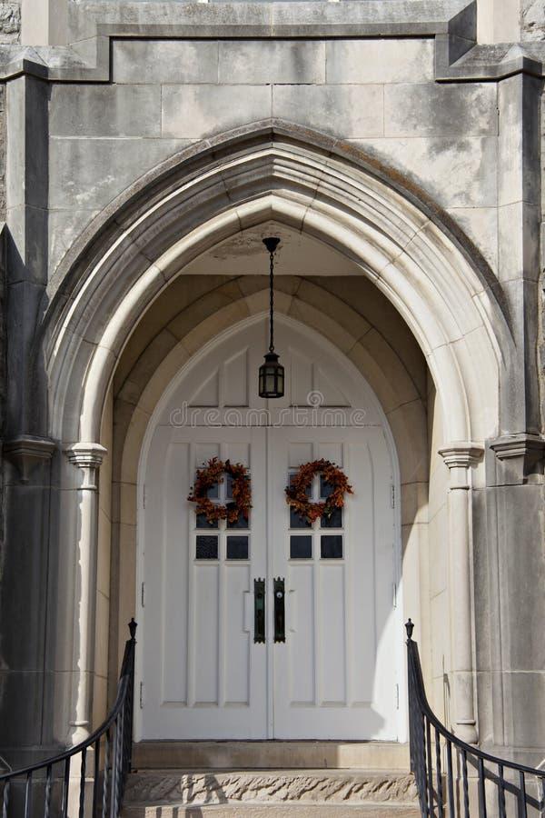 Las puertas catherdral blancas dobles surrouned por manera antigua de la entrada imágenes de archivo libres de regalías
