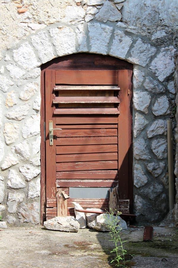 Las puertas cortas con los tableros de madera agrietados dilapidados se sostuvieron cerrado con las rocas grandes montadas en la  foto de archivo