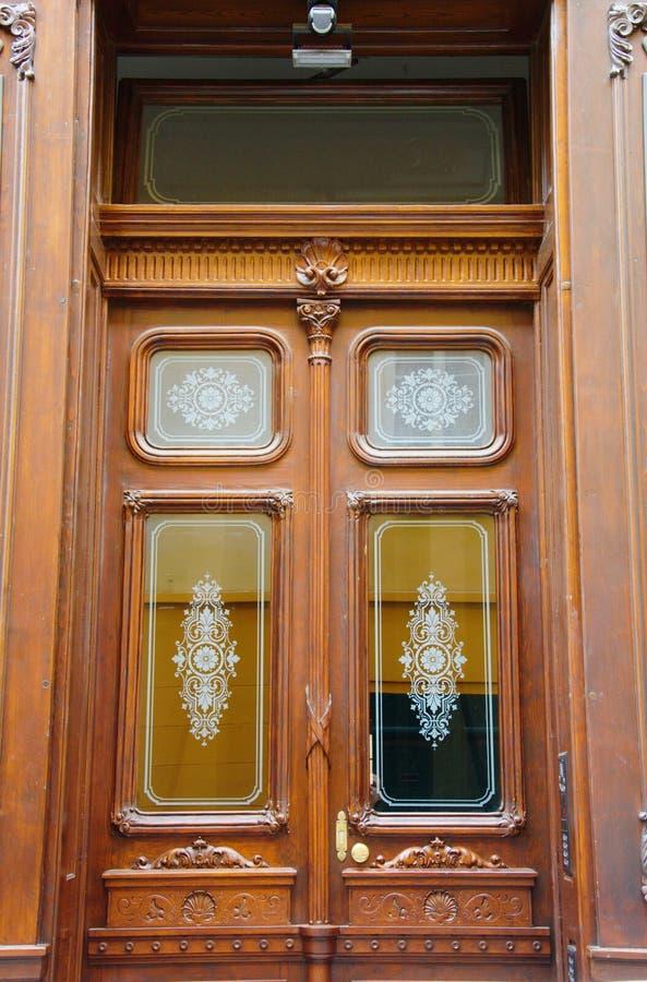 Las puertas de entrada dobles antiguas de madera hermosas con los rectángulos de cristal con blanco pintaron los ornamentos flora fotografía de archivo