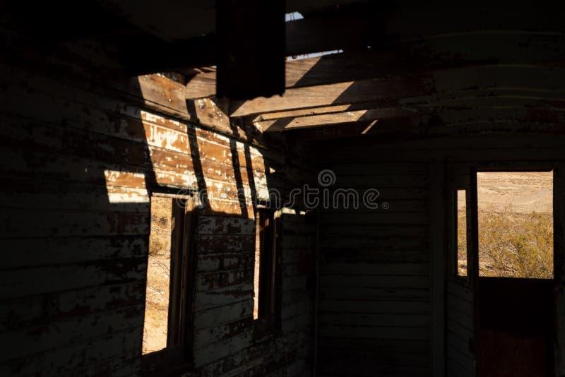 Las puertas de las ventanas abiertas de la opinión del desierto abandonadas entrenan al interior del caboose del coche de ferroca foto de archivo