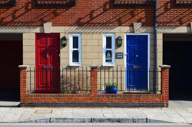 Las puertas vecinas rojas y azules en ladrillo emparedaron la casa del equipo imagen de archivo