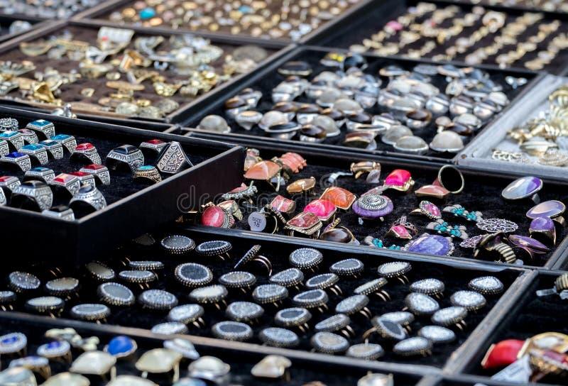 Las pulseras baratas de la joyería, anillos, pendientes vendieron en el mercado de pulgas fotografía de archivo