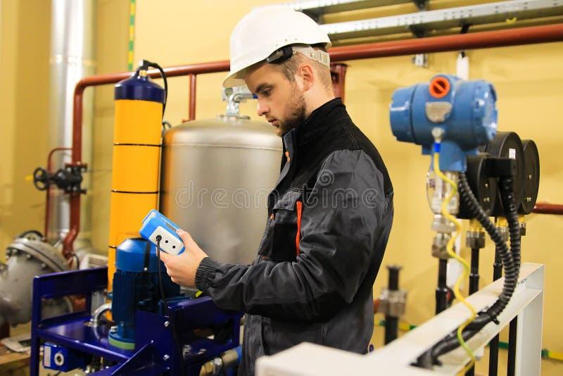 Las puntas de prueba cheking del ingeniero del técnico ejercen presión sobre los sensores en la planta de refinería industrial de foto de archivo libre de regalías