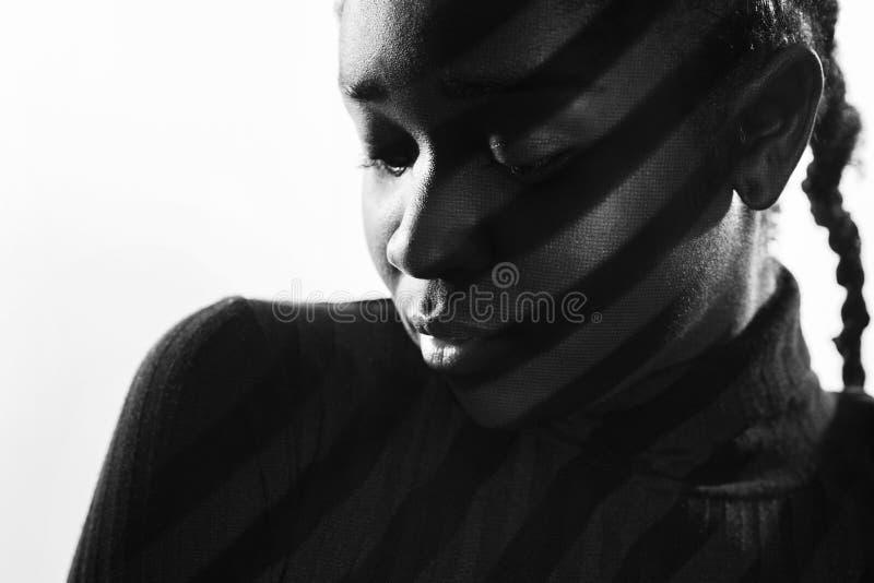 Las rayas creativas de la proyección se encienden en mujer hermosa con la piel oscura imagen de archivo