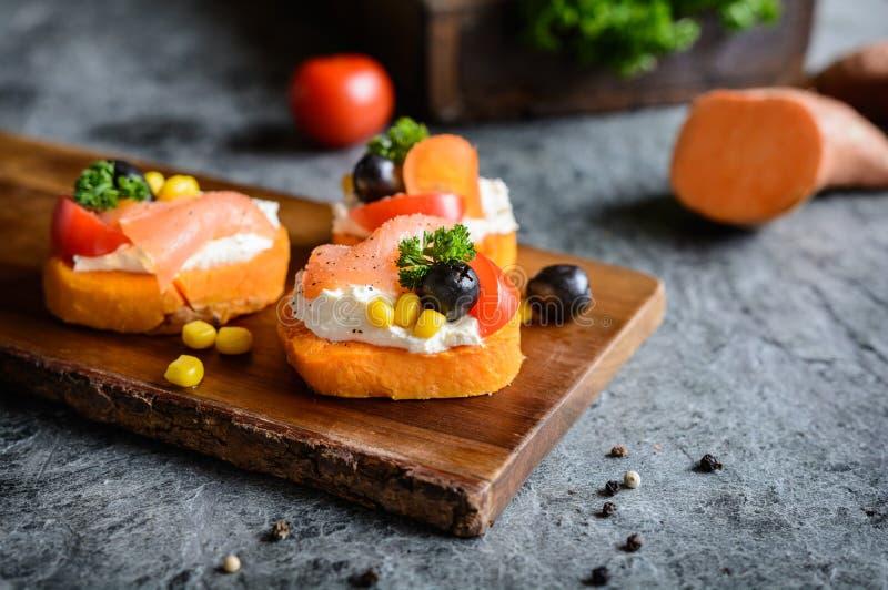 Las rebanadas de la patata dulce remataron con el queso cremoso, el salmón ahumado, las aceitunas y el maíz imagenes de archivo