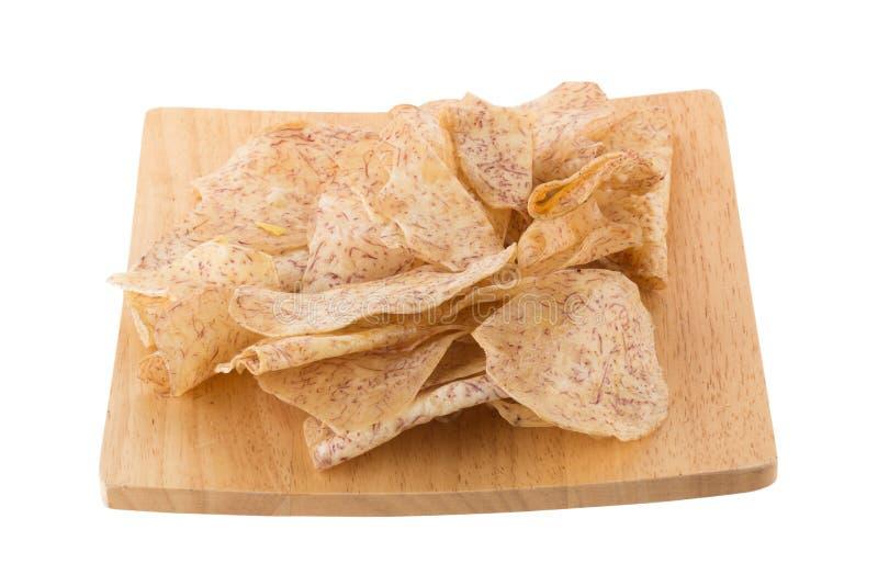 las rebanadas fritas del taro sumergen en el caramelo en una bandeja de madera aislada foto de archivo
