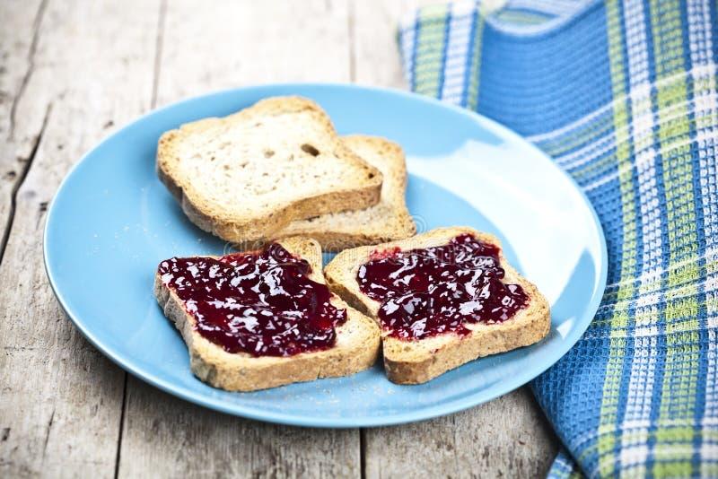 Las rebanadas tostadas frescas del pan del cereal con las bayas salvajes hechas en casa atascan y la servilleta de lino fotografía de archivo libre de regalías