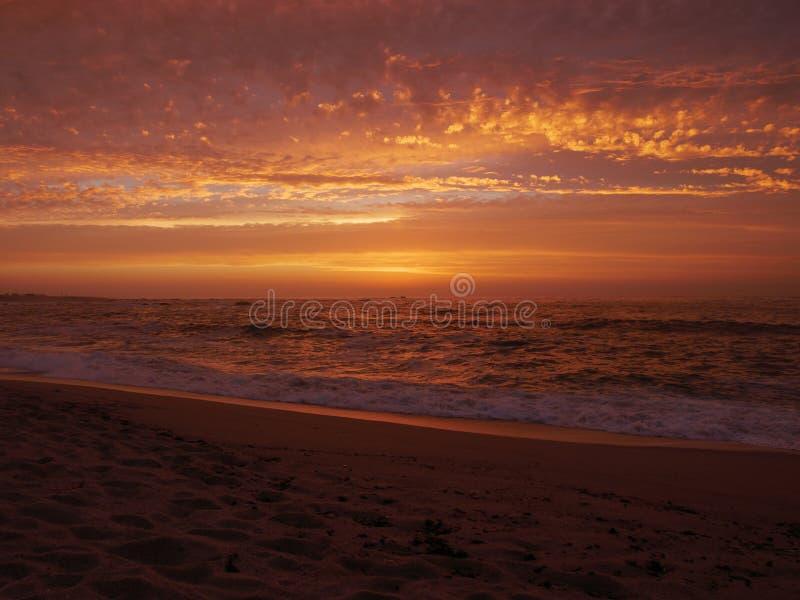 Las reflexiones en el agua en la puesta del sol en la playa como ondas se rompen en la arena fotografía de archivo libre de regalías