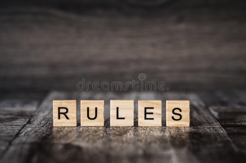 Las reglas de la palabra hechas de cubos de madera brillantes con las letras negras en a imágenes de archivo libres de regalías