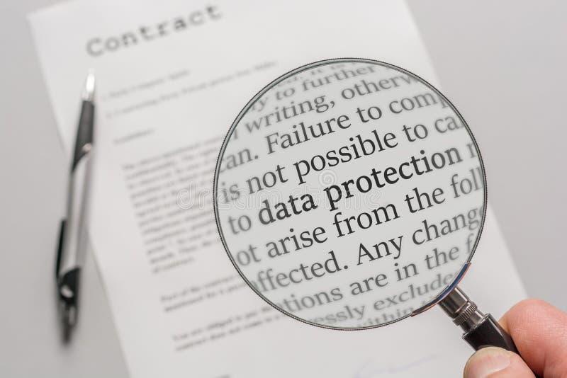 Las regulaciones de la protección de datos de un contrato se comprueban cuidadosamente con una lupa imagen de archivo libre de regalías