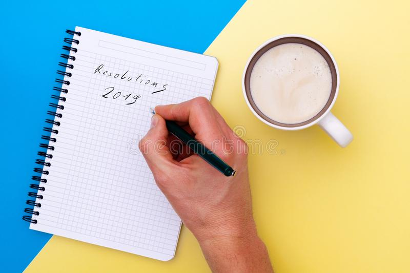 Las resoluciones masculinas de la escritura de la mano el año 2019, y acercan a estancias a la taza de café foto de archivo libre de regalías