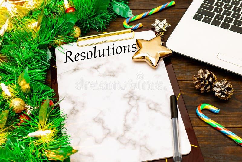 Las 2019 resoluciones y ordenador portátil con las ramas de árbol de navidad, estrella de oro, bastón de caramelo, conos del Año  foto de archivo