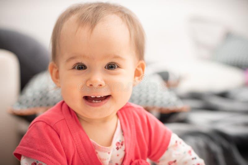 Las risas de 1 año lindas del bebé en ojos marrones grandes de la cámara y sonrisa amplia con nuevo echan los dientes, concepto d imagen de archivo libre de regalías