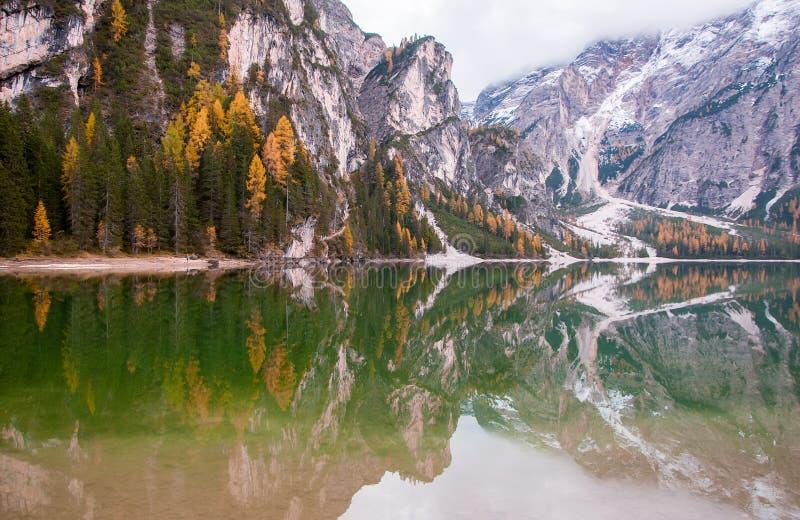 Las rocas de la montaña y el bosque del otoño reflejaron en el agua del lago Braies, montañas de la dolomía, Italia imagen de archivo libre de regalías