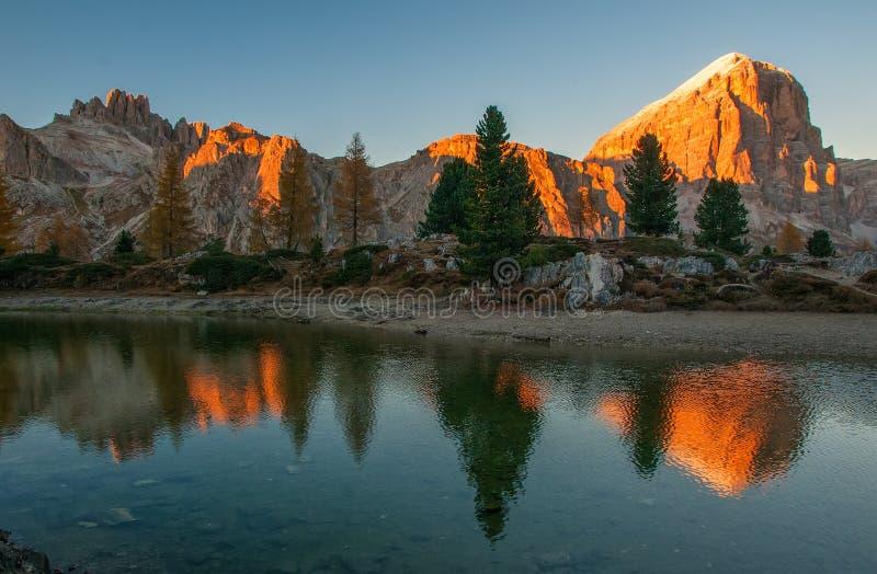 Las rocas de la montaña y los árboles del otoño reflejaron en el agua del lago en la puesta del sol, montañas de la dolomía, Ital foto de archivo libre de regalías
