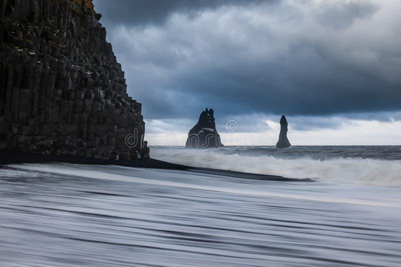 Las rocas del basalto pescan los dedos del pie con cebo de cuchara en la playa negra en la tormenta Reynisdrangar, Vik, Islandia imagenes de archivo