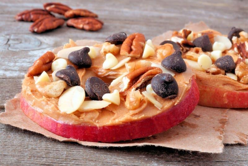 Las rondas de Apple se cierran para arriba con mantequilla, chocolate y nueces de cacahuete foto de archivo