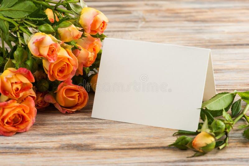 Las rosas anaranjadas frescas florecen, nota en blanco sobre fondo de madera imagen de archivo libre de regalías