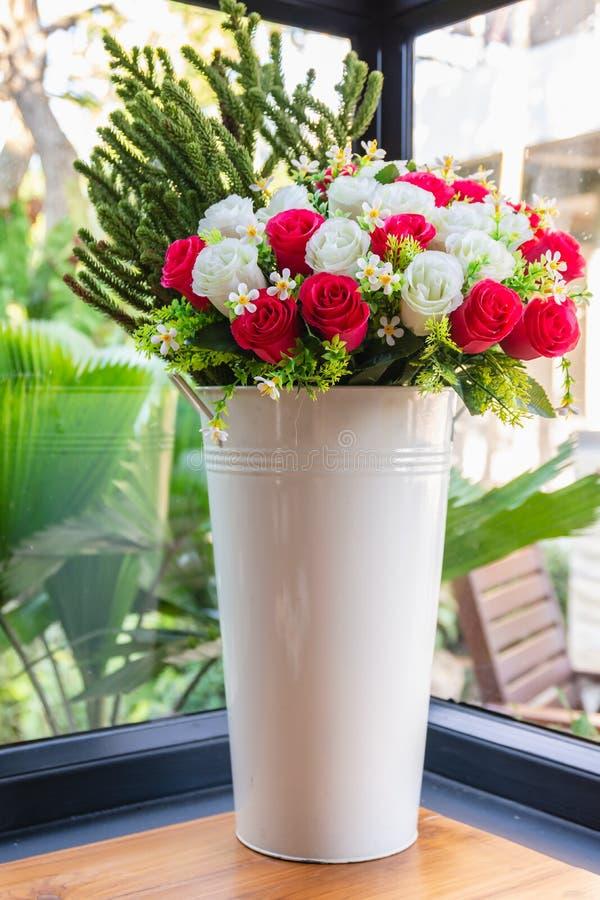 Las rosas coloridas florecen en florero blanco grande en el conner de la sala de estar foto de archivo